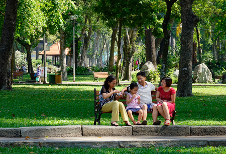Saigon, Vietnam - Dec 12, 2015. A family playing at the Tao Dan park in Saigon, Vietnam. Tao Dan Park is a very popular recreational site for local Vietnamese and tourists alike.