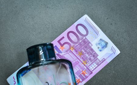 euromoney: Five hundreds (500) Euro banknotes, close up, with glass bottle of perfume background Stock Photo