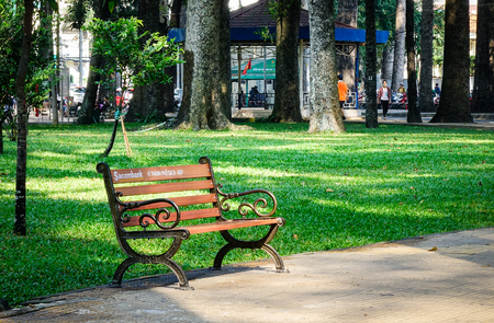 Saigon, Vietnam - Dec 12, 2015. A wooden bench at the Tao Dan park in Saigon, Vietnam. Tao Dan Park is a very popular recreational site for local Vietnamese and tourists alike. Editorial