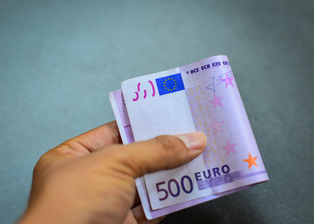 euromoney: A hand holding the Five hundreds (500) Euro banknote with gray stone wall background Stock Photo