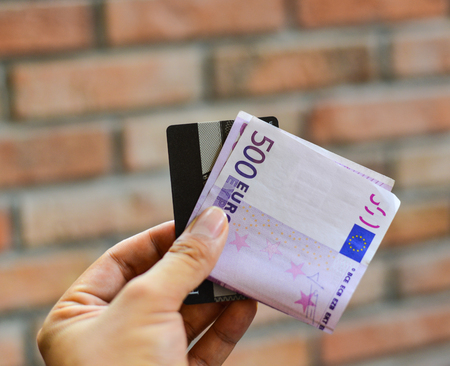 euromoney: A hand holding the Five hundreds (500) Euro banknote with credit card,  brick wall background