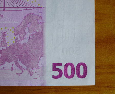 Detail of Five hundreds (500) Euro banknote with wooden table. Close up.