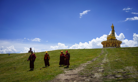 Sichuan, China - Aug 18, 2016. Monks with Big Buddha on the grass hill in Garze Tibetan, Sichuan, China. Tibetan Buddhism is historically the predominant religion practiced in Garze.