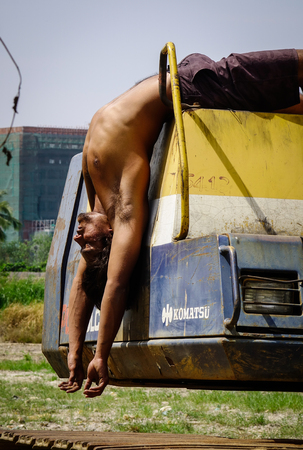 Delhi, India - Mar 9, 2017. A young worker doing exercise on the bulldozer in Delhi, India. Delhi is the fifth most populous city in the world and the largest city in India.
