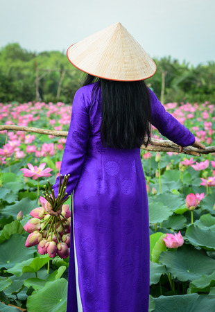 Vietnamese woman wearing traditional dress (ao dai) with conical hat and lotus flowers