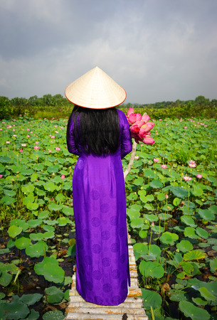 Vietnamese woman wearing traditional dress (ao dai) with conical hat and lotus flowers, standing on wooden bridge in countryside.