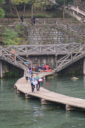 Hunan, China - Nov 6, 2015. People walking on wooden bridge in Fenghuang Ancient Town, China. Fenghuang is situated at the foot of mountains and beside waters. Editorial