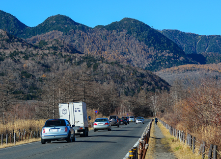magnificence: Nikko, Japan - Nov 4, 2014. Cars run on the road with mountain background in Nikko, Japan. Nikko is a popular destination for Japanese and international tourists.