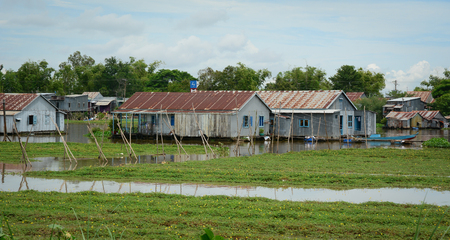 Wooden houses with vegetable field at floating village in An Giang, Vietnam. An Giang occupies a position in the upper reaches of the Mekong Delta. Stock Photo