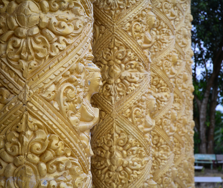 sight seeing: Golden columns with decoration at Khmer Buddhist temple. Close up. Stock Photo