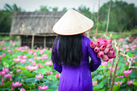 Asian woman in traditional dress with lotus flower, wooden house background.