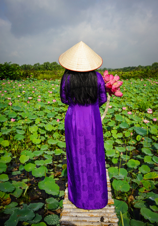 Asian woman in traditional dress with lotus flower, standing on wooden bridge.