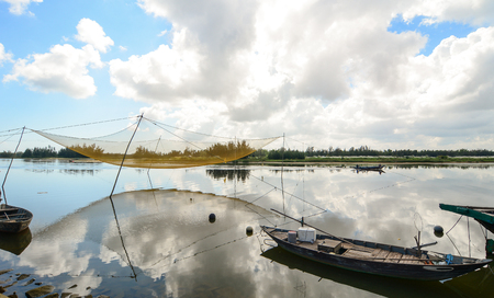River scenery with wooden boat and fishing net in Hoi An, Vietnam.