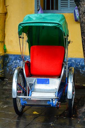 Cyclusriksja (cyclo) in Hoi An Town, Vietnam. Cyclusriksja's worden veel gebruikt in grote steden in Zuid-, Zuidoost- en Oost-Azië. Stockfoto - 74507910