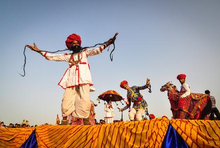 Pushkar, INDIA - 7 maart 2012. Rajasthani volksdansers in kleurrijke etnische kleding presteren in Pushkar, India. Pushkar is een stad in het Ajmer-district in de Indiase deelstaat Rajasthan. Stockfoto - 74751521