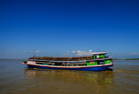 Mandalay, Myanmar - Oct 18, 2015. A wooden cargo boat on Ayeyarwady River in Mandalay, Myanmar. Ayeyarwady is the country largest river and most important commercial waterway. Editorial
