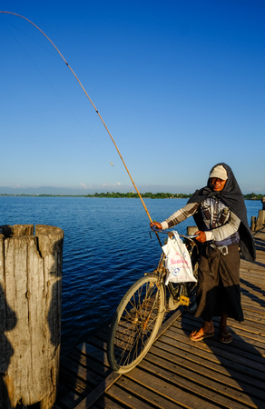 Mandalay, Myanmar - Oct 18, 2015. People with the bicycle on Ubein Bridge in Mandalay, Myanmar. The bridge is believed to be the oldest and longest teakwood bridge in the world.