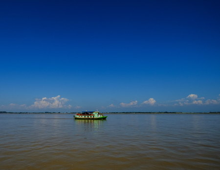 A wooden ferry runs on Ayeyarwady River in Mandalay, Myanmar. Ayeyarwady is the country largest river and most important commercial waterway. Banco de Imagens