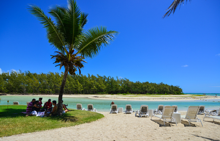 Flacq, Mauritius - Jan 12, 2017. People sitting on the sand beach in Ile Aux Cerfs Island, Flacq, Mauritius. The island is one of the must place to visit and see in Mauritius.