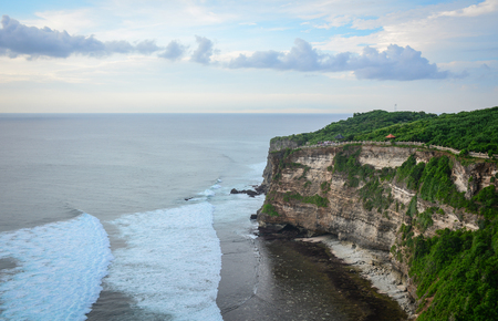 Pura Uluwatu temple with cliff in Bali island, Indonesia. The temple is one of the nine directional temples of Bali meant to protect it from evil.