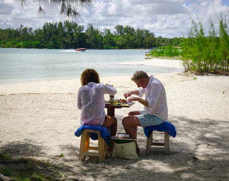 reputed: Flacq, Mauritius - Jan 12, 2017. Tourists enjoy lunch on beach in Ile aux Cerfs, Mauritius. Ile aux Cerfs is by far the most popular and reputed island destination in Mauritius. Editorial