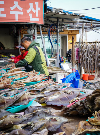 million fish: Busan, Korea - Nov 2, 2014. People making dried fish at the local village in Busan, Korea. Busan (Pusan) is Korea second largest city with close to 4 million people.