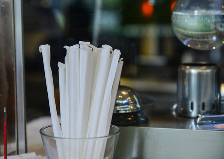 White straws in glass at the kitchen of coffee shop. Close up.