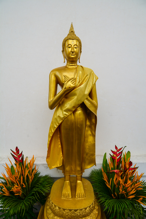 BANGKOK, THAILAND - JUL 30, 2015. Golden Buddha statue with flowers at Wat Intharawihan in Bangkok, Thailand. The temple is known for its enormous 32 meters high standing Buddha.