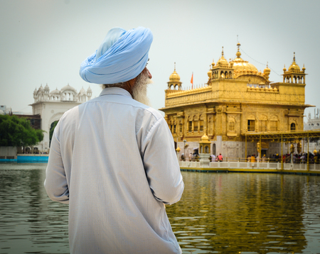 spiritual architecture: Amritsar, India - Jul 25, 2015. An old man praying at the Golden Temple in Amritsar, India. Golden temple is also known as Harmandir Sahib, a significant Sikh temple, which is located in Amritsar.