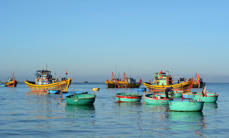 Phan Thiet, Vietnam - Mar 19, 2016. Wooden boats docking on the sea at sunny day in Mui Ne town, Phan Thiet, Vietnam. Mui Ne is a coastal fishing town in the Binh Thuan Province, Vietnam.