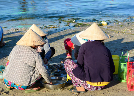 Phan Thiet, Vietnam - Mar 19, 2016. Group of women with conical hat sitting at pier in Mui Ne town, Phan Thiet, Vietnam. Mui Ne is a coastal fishing town in the Southern Vietnam.