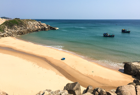 Beautiful sand beach with wooden boats on the sea at sunny day