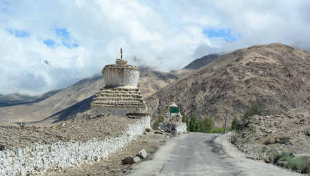 The mountain road with Buddhist stupas at sunny day in Leh, Ladakh, India. Ladakh is one of the most sparsely populated regions in Jammu and Kashmir. Stock Photo