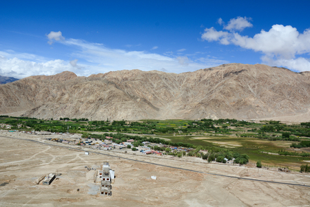 m: Mountain scenery with a Tibetan village in Leh, Ladakh, India. Ladakh is the highest plateau in the state of Jammu & Kashmir with much of it being over 3,000 m. Stock Photo