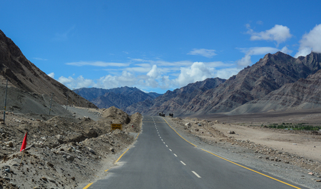 National road with mountain background at sunny day in Leh, Ladakh, India. Ladakh is one of the most sparsely populated regions in Jammu and Kashmir.