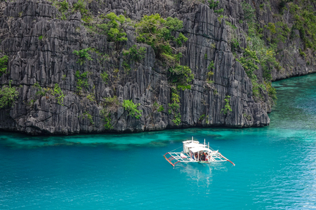 Coron, Philippines - Apr 9, 2017. A wooden boat carrying tourists on the Kayangan Lake in Coron Island, Philippines. Coron has been described as one of the best spots in the World for Wreck diving.