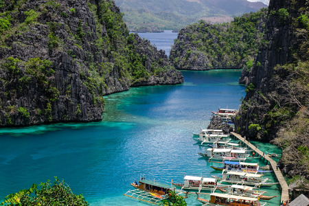 nido: Coron, Philippines - Apr 9, 2017. Many wooden boats docking on the Kayangan Lake in Coron Island, Philippines. Kayangan Lake is an isolated volcanic lake in the middle of Coron Island. Editorial