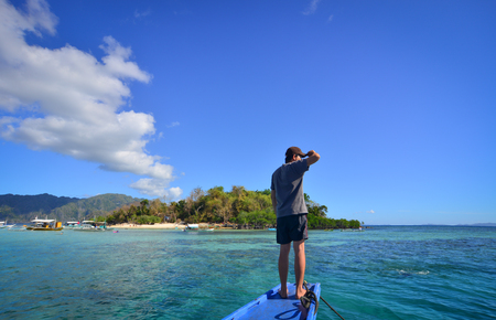 nido: Landscape of tropical sea at sunny day. An Asian man standing on wooden boat and looking at the blue sea.