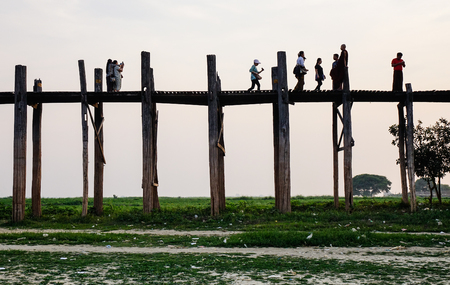 Mandalay, Myanmar - Feb 20, 2016. People walk on U Bein Bridge in Mandalay, Myanmar. The teak bridge is a crossing that spans the Taungthaman Lake near Amarapura in Myanmar. Editorial