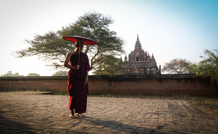 A Buddhist monk with red umbrella at the ancient temple in sunny day.