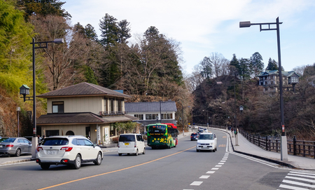 magnificence: Nikko, Japan - Jan 2, 2016. Vehicles run on main street at sunny day in Nikko, Japan. Nikko is a popular destination for Japanese and international tourists. Editorial