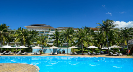 inground: Phan Thiet, Vietnam - Oct 14, 2015. Swimming pool with relaxing chairs at luxury resort in Phan Thiet, Vietnam. Phan Thiet is a coastal city famous for many luxury resorts runing along the coast.