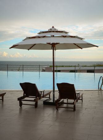 inground: Swimming pool with relaxing chairs at luxury resort in sunset Editorial