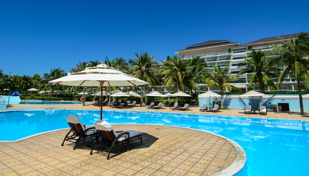 inground: Phan Thiet, Vietnam - Oct 14, 2015. Swimming pool of luxury resort at sunny day in Phan Thiet, Vietnam. Phan Thiet is a coastal city famous for many luxury resorts runing along the coast.