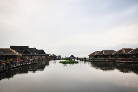 Wooden houses on Inle lake at rainy day in Shan state, Myanmar. The Inle Lake is famous for its floating villages and the unique way of life of Intha people. Stock Photo