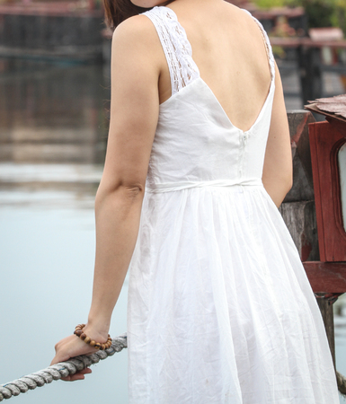 Young Asian woman in white dress standing at luxury resort.