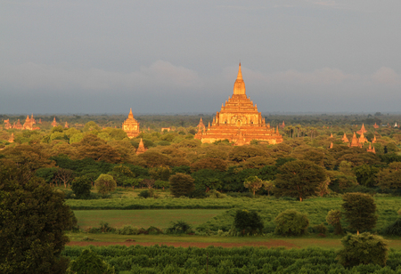 nascent: Ancient Buddhist temples with green trees at sunset in Bagan, Myanmar. The Bagan Archaeological Zone is a main attraction for the country nascent tourism industry.