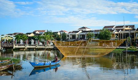 Hoi An, Vietnam - 28 november 2015. Een man roeiboot op de Hoai-rivier in de oude stad van Hoi An, Vietnam. Hoi An is Vietnam's meest sfeervolle en heerlijke stad. Stockfoto - 76812317