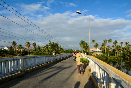 Hoi An, Vietnam - Dec 6, 2015. People walk on an old bridge in Hoi An, Vietnam. Ancient and peaceful, Hoi An is one of the most popular destinations in Vietnam.