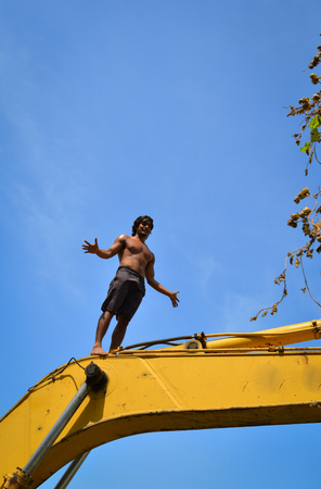 An Indian young man standing on the construction machine
